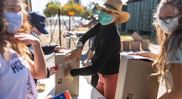 Volunteers packing boxes wearing breathing masks